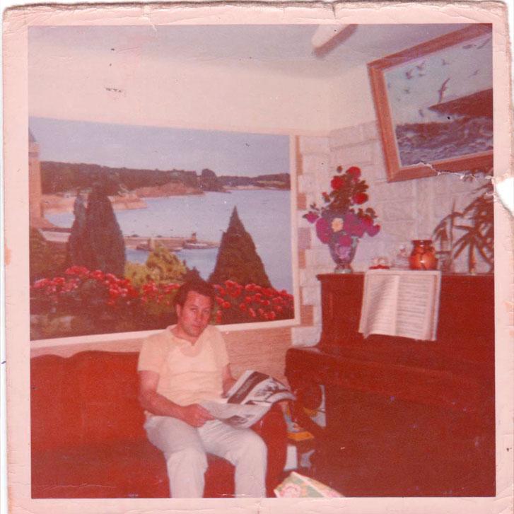 Le papa de la créatrice Charles Landston devant ses tableaux et son piano