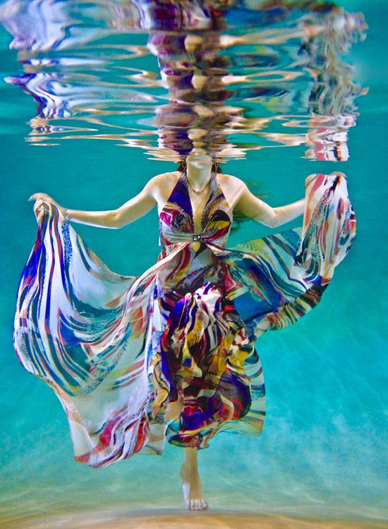 Styles de femme - Femme artistique - Elle se trouve dans une piscine portant une robe longue avec un décolleté en V dos-nu. Sa robe est très haute en couleurs et flotte et danse dans l'eau