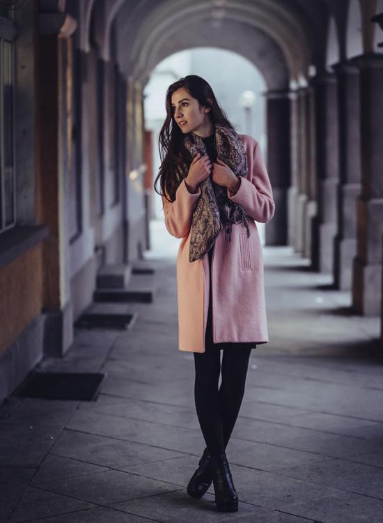 Femme élégante Elle porte un manteau trois quart rose, un foulard et un colland noir chaussée de bottines noires