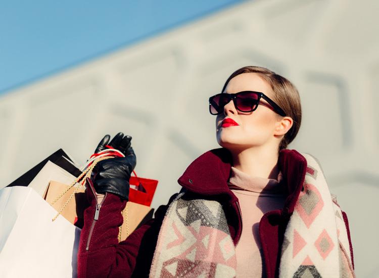 Femme sophistiquée - Elle porte un manteau bordeau à grand col, des gants noirs en cuir, une écharpe aux motifs géométriques daans les tons roses. Elle porte un paire de lunette de soleil. Elle est bien maquillée