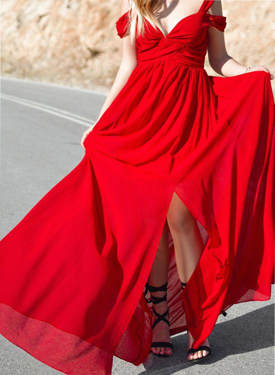 Styles de femme - Femme glamour - Cette femme porte une robe longue rouge fendue sur le devant. Elle a un décolleté en V sans manche, elle est chaussée de talons aiguilles noirs