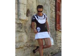 Charles Landston portant le T-shirt femme tête de mort de Charles Landston, avec une jupe courte blanche très féminine. Une matière idéale poure