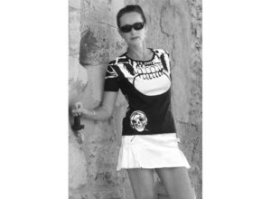 T-shirt femme tête de mort en microfibre by Charles Landston. Charles Landston portant le t-shirt ave un jupe courte blanche. Très féminin