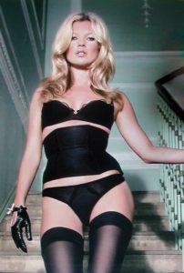 Le dressing idéal - Kate Moss porte une lingerie noire et des gants en cuir noir. Le haut est une corbeille et le bas est une culotte en voile noir puis des bas autofixants