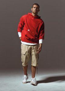 Homme de morphologie H - Un sweat à capuche rouge avec en dessous un t-shirt blanc à manche longue associé à un bermuda beige et des baskets blanches