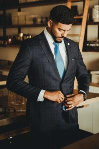 Homme de morphologie V - Un homme porte un blazer foncé de couleur avec une chemise blanche et une cravate bleue claire. Accessoires : pochette, montre, chevalière