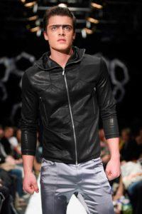 Morphologie Trapèze - Un homme porte un pantalon ajusté gris perle satiné et d'un blouson noir près du corps