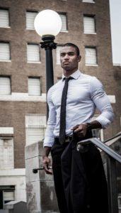 Homme de morphologie O - Un homme porte une chemise blanche très ajustée avec une cravate noire