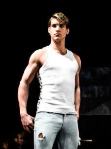 Homme de morphologie V - Un jeune homme porte un débardeur blanc cintré et ajusté avec un jeans ajusté