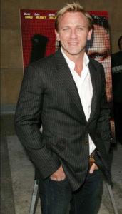 Morphologie Trapèze - Daniel Craig est habillé d'un blazer noir avec des rayures verticales, d'une chemise blanche et d'un jean noir