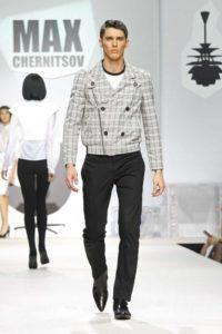 Morphologie Trapèze - Un homme porte un pantalon ajusté de forme cigarette et d'un blouson à carreaux de couleur gris perle