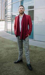 Un homme porte un blazer rouge brique avec une écharpe, un pantalon gris et des chaussure de ville noires