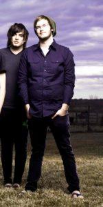 Homme de morphologie O - Un jeune homme porte une chemise bleue violette par dessus le pantalon qui est un jean de coupe droite