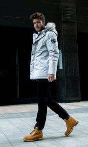 Homme de morphologie A - Un homme porte une parka à capuche avec un pantalon droit et des boots montantes
